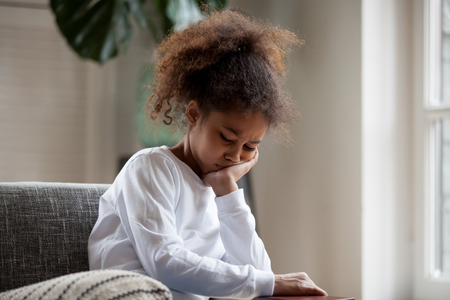 Upset little african american girl feels hurt sad bored sitting alone at home, depressed punished mixed race kid having psychological trauma, frustrated preschool black child thinking hiding problem