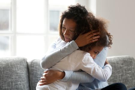 Amorevole madre single nera che abbraccia figlia africana accarezzando coccole, mamma premurosa che abbraccia ragazza di supporto, mamma e bambino relazioni sincere affettuose, affidamento, custodia dei figli, concetto di adozione