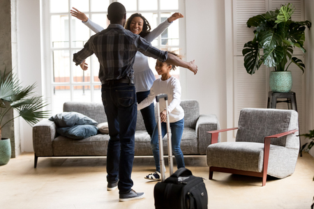 Happy loving black family wife and kid daughter excited to meet hurry to hug dad with suitcase coming returning home arriving from long business trip, welcome back african father, reunion concept