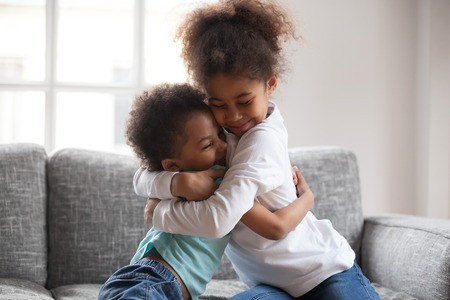 Cute happy african american siblings hugging cuddling feeling love and connection, smiling mixed race kid girl sister embracing little boy brother sitting on couch, 2 children good relationships Фото со стока