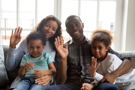 Happy african american family with 2 kids son daughter waving hands looking at camera, portrait of smiling black mom dad and children talking at webcam saying hello making online video call or vlog