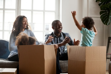 Excited mixed race kids jumping out of box playing with mom dad in living room, african joyful children having fun laughing packing unpacking with black parents, family moving in new home relocation