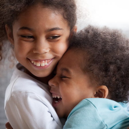 Cute african american kids with funny faces hugging laughing, 2 siblings boy and girl embracing having fun together, little brother and sister cuddling feeling connection, close up view, square crop