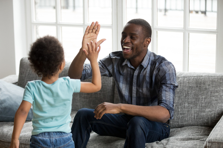 Happy black dad and little son giving high five playing at home, excited african single father and toddler cute kid boy laughing enjoying clapping hands having fun together, daddy child friendship