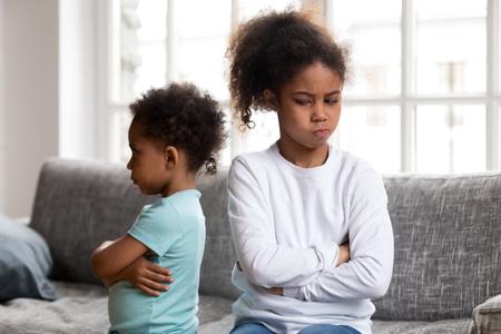 Wütende, hartnäckige afrikanische Vorschulmädchenschwester und beleidigter kleiner Junge, der sich gegenseitig ignoriert, sitzt auf der Couch, fühlt sich eifersüchtig und vermeidet Gespräche, 2 Kinderkonflikte, Geschwisterrivalität schlechte Beziehung