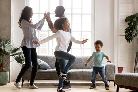Gelukkige afro-amerikaanse familie en grappige actieve kinderen die plezier hebben met dansen samen in een nieuw huis, vrolijke zwarte ouders en twee kinderen die genieten van bewegen op muziek, weekendtijd doorbrengen in de woonkamer