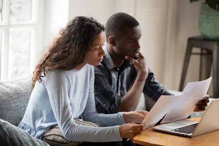 Serious worried african american couple reading documents consider mortgage loan insurance contract terms, focused black man and woman holding checking bank papers at home, domestic bills concept Imagens - 115425431