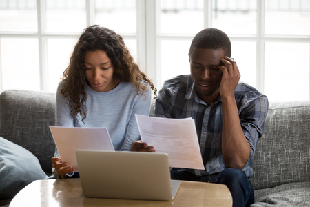 Serious concerned african american couple renters tenants holding domestic utility bills reading papers documents at home, stressed millennial black bank clients having debt loan money problems