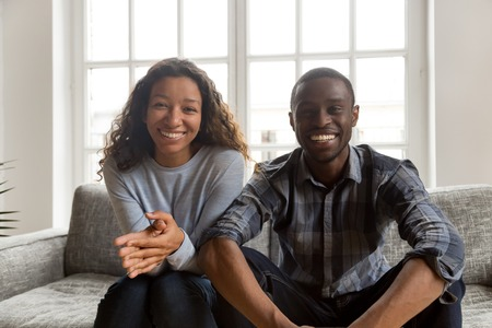 Happy friendly african couple looking at camera at home, smiling black husband and wife making video call, cheerful american man and woman millennial vloggers recording video blog headshot portrait