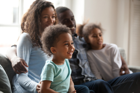 Happy black family with children sitting on couch watching tv together, african american parents embrace kids relaxing on sofa laughing enjoying funny cartoons or movie having fun on weekend at home Banco de Imagens