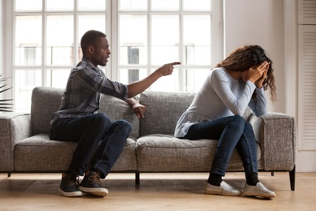 Angry black husband arguing yelling blaming upset wife of problems, jealous distrustful dominant african american boyfriend controlling shouting at sad girlfriend, quarrelling family fight at home Foto de archivo - 115425527