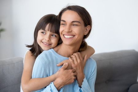 Happy family of smiling single mom and cute kid daughter embracing looking into bright future thinking of good, little child girl embracing young loving mother dreaming planning new goals concept Stockfoto