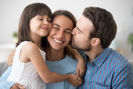 Loving husband and cute kid daughter embracing kissing happy mom wife on cheek congratulating with mothers day, little child girl and dad hugging smiling mum, caring family of three bonding together Standard-Bild