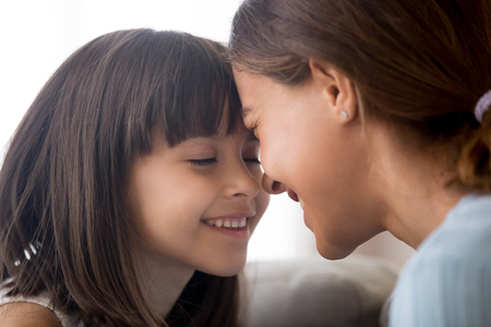 Smiling little child girl enjoying tenderly touching foreheads with happy mom, cute kid daughter and mother having fun bonding feeling love connection enjoy time together, sincere warm relationships