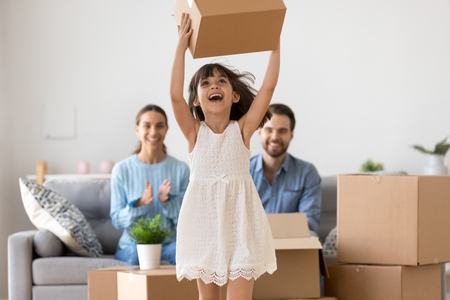 Cute happy kid girl holding box jumping having fun relocating into new modern home or apartment with parents, excited child daughter playing with cardboard box enjoying family moving day concept Banque d'images