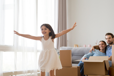 Cute small kid feels happy playing on moving day concept, active happy girl running over living room exploring new apartment, excited child having fun in modern home with parents after relocation Imagens