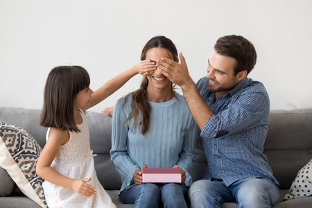 Happy child daughter and husband congratulating mom celebrating birthday at home together closing eyes of smiling mum holding pink gift box, kid and dad make surprise present on mothers day holiday Archivio Fotografico