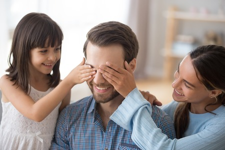 Happy loving wife with kid daughter congratulate excited dad with fathers day at home, mom with little child girl closing eyes of smiling daddy make pleasant secret surprise on birthday or holiday Stock Photo