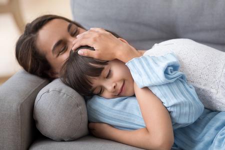 Madre amorevole che accarezza la piccola figlia carina sdraiata sul divano insieme, mamma premurosa che abbraccia il bambino che si rilassa godendosi il pisolino, mamma felice che accarezza abbracciando la ragazza in età prescolare che stringe a sé che riposa sul comodo divano