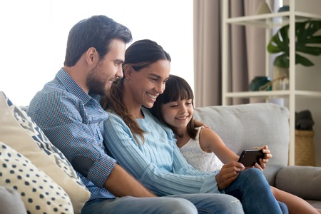 Beautiful family of mom dad and little kid child daughter sitting together on sofa smiling looking at smartphone screen taking selfie, making video call or recording vlog with cellphone at home Stockfoto