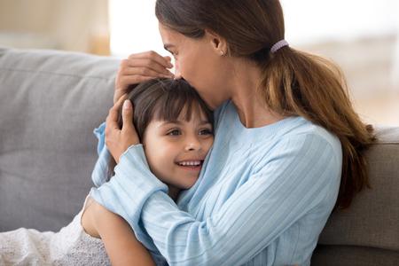 Liebevolle alleinerziehende Mutter, die süße kleine Tochter umarmt, die das Kind küsst, das auf dem Sofa sitzt, glückliche Mutter, die das Vorschulmädchen streichelt, Mütter kümmert und unterstützt, aufrichtige warme Beziehungen für das Kinderkonzept