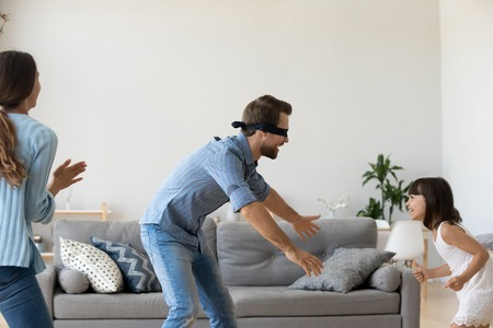 Blindfolded father playing hide and seek game with family at home, cute child daughter runs from dad having fun, parents kid girl laughing spending time together enjoy weekend activity in living room Zdjęcie Seryjne