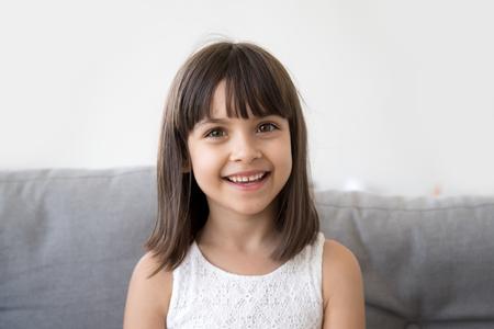 Schattige schattige kleine vlogger die naar de webcam kijkt, glimlachend kindmeisje dat met de camera praat en videogesprek voert, vlog online communiceert zittend op de bank thuis, gelukkig voorschools kind headshot portret