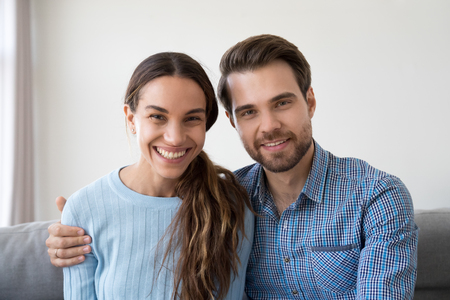 Headshot portrait of happy smiling millennial couple sitting on sofa at home embracing looking at camera, young man and woman making video call communicating online or recording vlog together