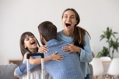 Opgewonden vrouw en kind dochter knuffelen vader die terugkeert na een lange reis met koffer, gelukkige vader omhelst verraste liefhebbende familie die vermiste papa verwelkomt die terug naar huis komt, reünieconcept
