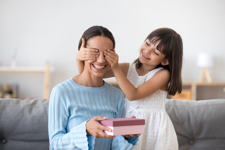 Smiling child daughter closing eyes of excited mom holding pink gift box congratulating mum celebrating birthday with mommy at home together, cute kid girl making surprise present on mothers day Stock Photo