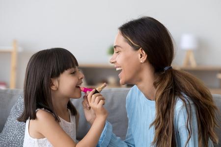 Felice mamma e figlia in età prescolare che fanno il trucco insieme mettono il rossetto, bambina divertente che applica il trucco sulle labbra delle madri, bambino che si diverte a giocare con la mamma sorella seduta sul divano a casa Archivio Fotografico