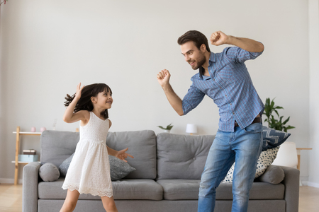 Happy dad and little funny daughter laughing dancing in living room, cheerful daddy and cute child girl having fun together, active kid enjoying copying fathers moves playing with parent at home Archivio Fotografico