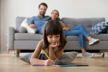 Cute kid girl playing on warm floor at home, preschool little girl drawing with colored pencils on paper spending time with family in living room, creative child activity, underfloor heating concept Banco de Imagens