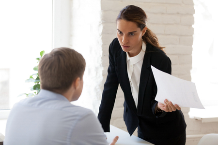 Serious businesswoman blaming employee for mistake in paper document, financial report, dissatisfied woman, ceo, team leader arguing with worker about bad work results, failure, business problem