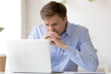 Focused puzzled businessman looking at laptop screen, thinking about business problem, tired exhausted man checking document, solving difficult work, computer task, worried about job mistake