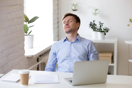 Sleepy businessman with closed eyes relaxing at workplace after finished work with laptop, overworked man meditating during break, breathing, tired exhausted entrepreneur sleeping at work