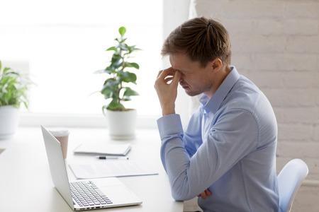 Hombre de negocios cansado masajeando el puente de la nariz, sintiendo tensión en los ojos, malestar, hombre agotado que sufre de síndrome de visión por computadora después de un uso prolongado de la computadora portátil, relajación de la vista, problema de salud