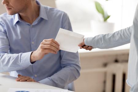 Gros plan sur un homme d'affaires prenant une enveloppe avec un pot-de-vin d'une femme, un client donnant, offrant de l'argent à un homme malhonnête, faisant un accord illégal secret, des partenaires planifiant une fraude, vue des mains, concept de corruption Banque d'images