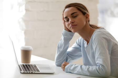 Tired woman sitting with closed eyes half asleep at workplace, lazy student, businesswoman disinterested in boring routine work, sleeping on hand during break, falling asleep at desk, insomnia Banco de Imagens