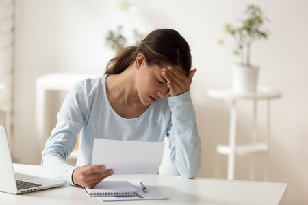 Upset stressed woman reading dismiss or debt notification, sitting at home or in office, bad news receiving concept, frustrated female student holding paper document, failed exam, rejection