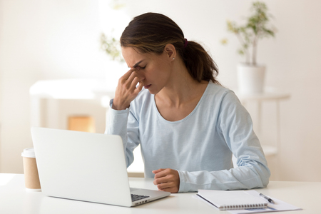 Upset woman feeling tired after long hours computer work, sitting at workplace, massaging nose bridge, bad vision concept, businesswoman, student suffering from eye strain, fatigue after laptop use Stock Photo