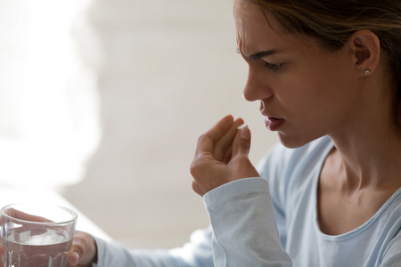 Close up unhealthy woman hold glass still water and painkiller pill, taking antidepressant or antibiotic medicine, sick female suffering from headache or insomnia, emergency treatment concept close up Stock Photo