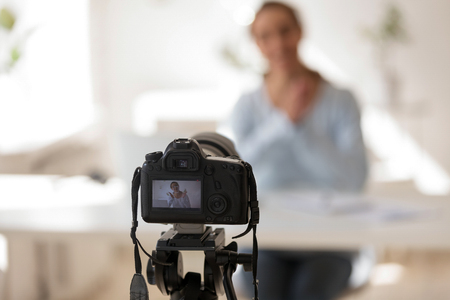 Businesswoman recording video blog on professional digital equipment, modern business coach making presentation for website or webinar, create content for video blog channel, focus on camera