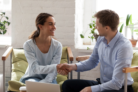 Smiling happy woman shaking hand of confident businessman, getting acquaintance with new business partner, making deal, greeting, introducing to client, successful negotiation, agreement 版權商用圖片