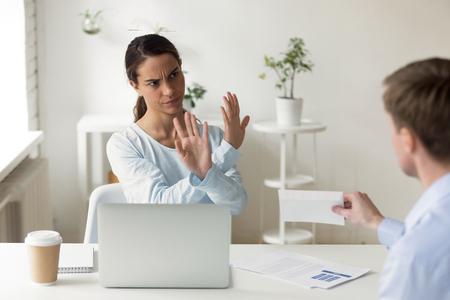 Outraged businesswoman refusing, denying envelope with bribe at workplace, showing no to man with money, reject, disagree with making illegal dishonest deal, stop bribery and corruption concept Stock Photo