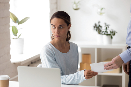 Worried woman taking envelope with bribe, money from person at workplace, colleagues, business partners planning fraud, making secret illegal deal in office, corruption concept