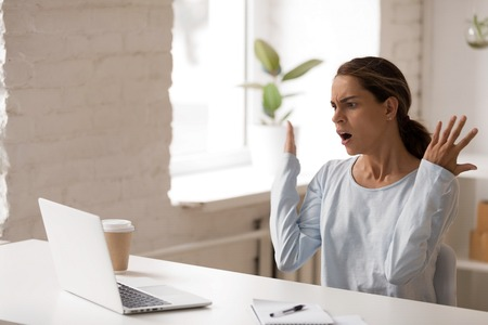 Unpleasantly surprised woman looking at laptop screen, sitting with raised hands, gesture, receiving bad unexpected news, outraged shocked businesswoman reading business email, bankruptcy Foto de archivo