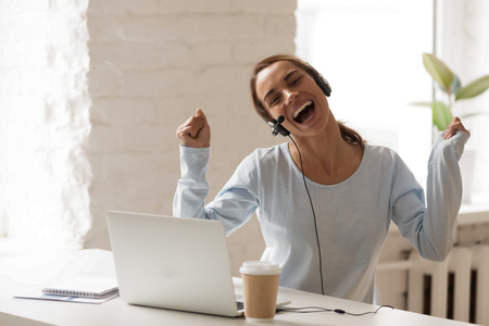 Fröhliche Frau in Kopfhörern mit Laptop, singen und tanzen in der Pause, bewegen sich im Rhythmus mit Lieblingsmusik, glückliche Frau im Headset genießen, online lernen, E-Learning