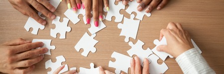 Top above close up hands diverse team assembling jigsaw puzzle joining pieces at desk search right solution, successful teamwork help support concept, horizontal photo banner for website header design