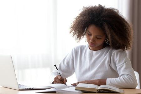 Focused African American teenage girl sit at table with laptop studying with handbooks, serious concentrated black teenager do homework at home, write down in notebook, using computer and textbook Banco de Imagens